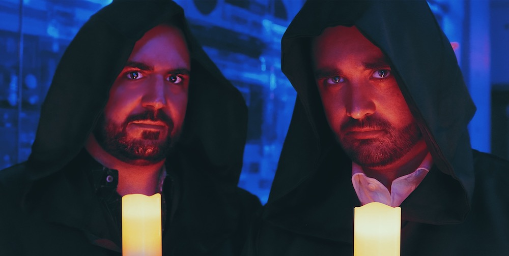 Magicians Harrison Greenbaum & Patrick Davis wearing cloaks and dramatically holding candles.