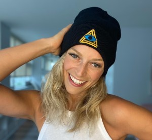 Woman wearing a black beanie with the RECON logo.