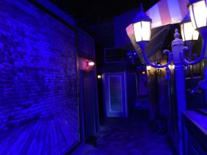 A dimly lit main street in Bold Escape Room's. The doors are the entrances to their games.