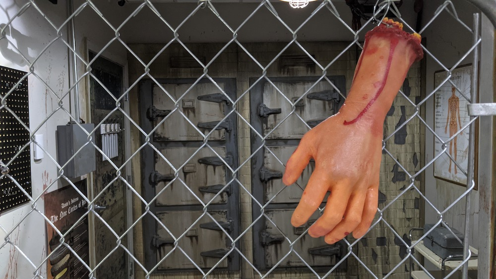 A fake severed hand bound to a chainlink fence in a morgue.