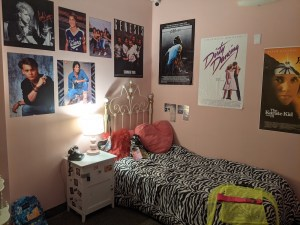 A teen girl's bedroom in the 1980s, posters from various movies and bands cover the walls.