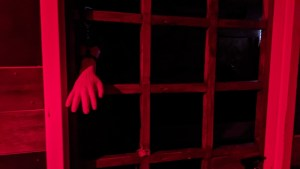 A severed hand chained to a wooden gate.