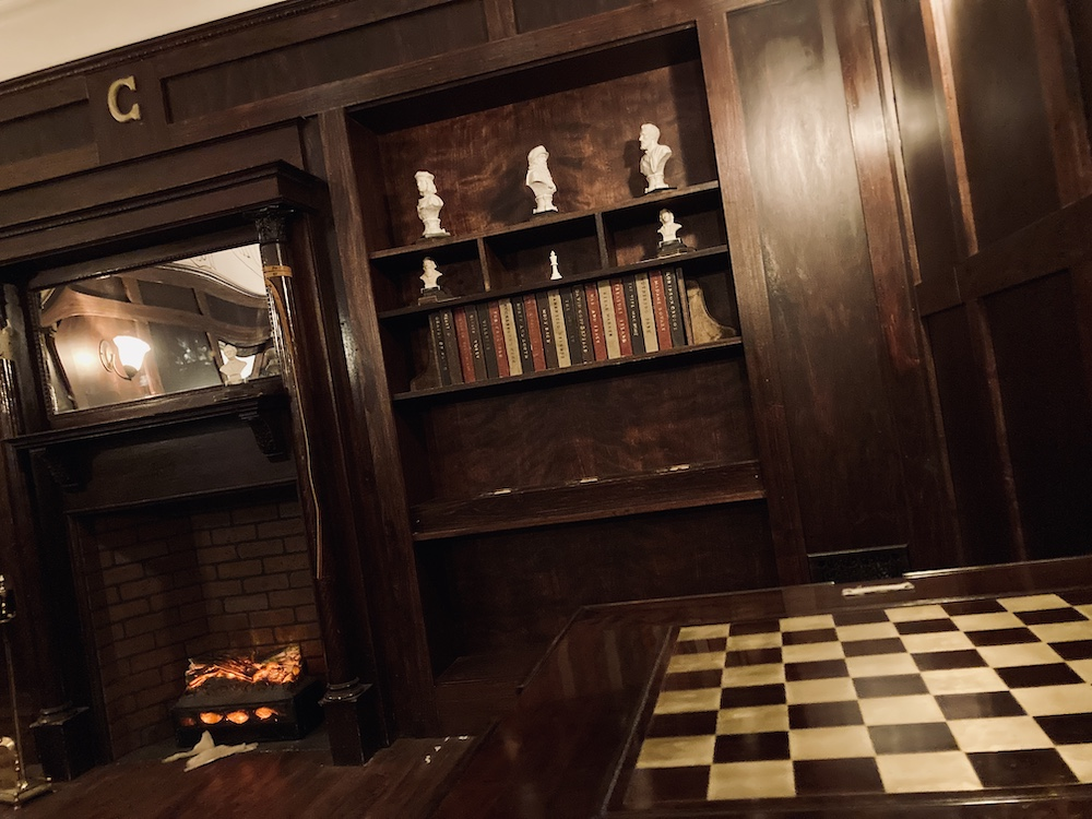 In-room: a bookshelf, fireplace, and chess board in a study.