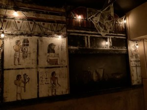 A wall of hieroglyphics lit by a string of lights. .