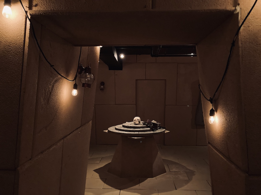 In-room: A corridor in an ancient Egyptian tomb. At the end of it is a chamber with a table and a skull.