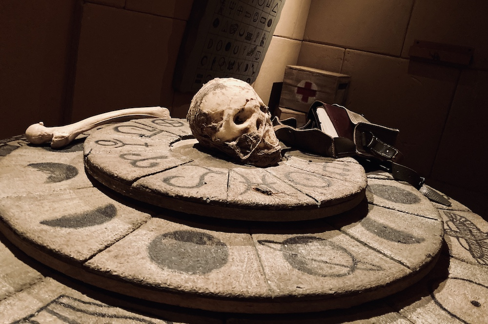 In-room: A wheel with multiple levels, covered with symbols in an Egyptian tomb. A skull, satchel, and femur bone sit atop.