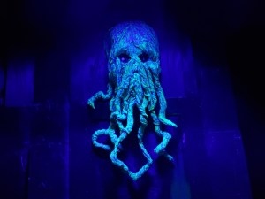 A sculpted head of Cthulhu dramatically lit.