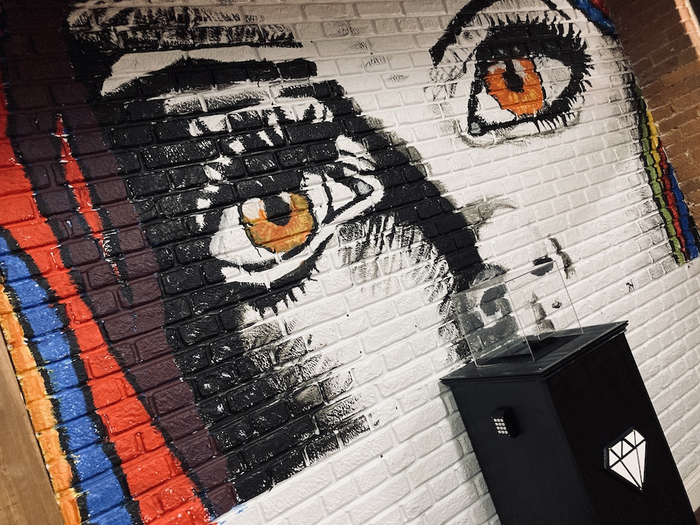 A massive mural of a woman's eyes painted on a brick wall. Below it is a display case for a diamond.