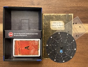 Cemetery of the Night box contents includes a deck of cards, a journal, a transparency, and a solution wheel.