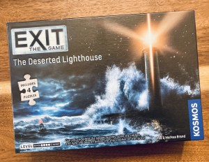 Exit Deserted Lighthouse box art depicts an illuminated lighthouse in the middle of rough seas at night.