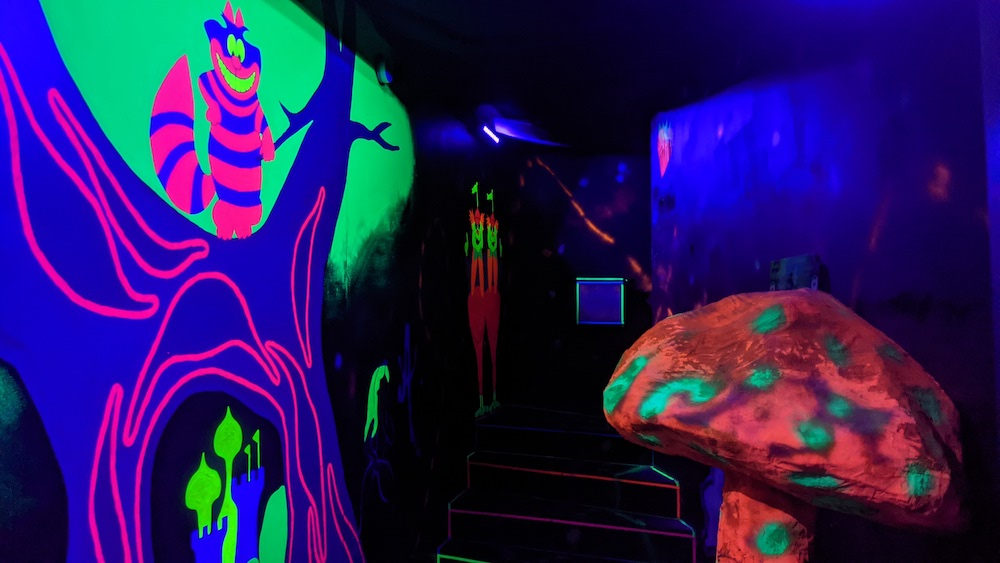 Blacklight illuminated Alice in Wonderland set with a glowing mushroom and Cheshire Cat.