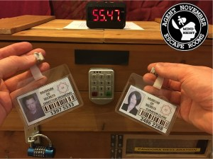 First person view, a pair of hands holding two security badges in front of a locked box with a timer on it.