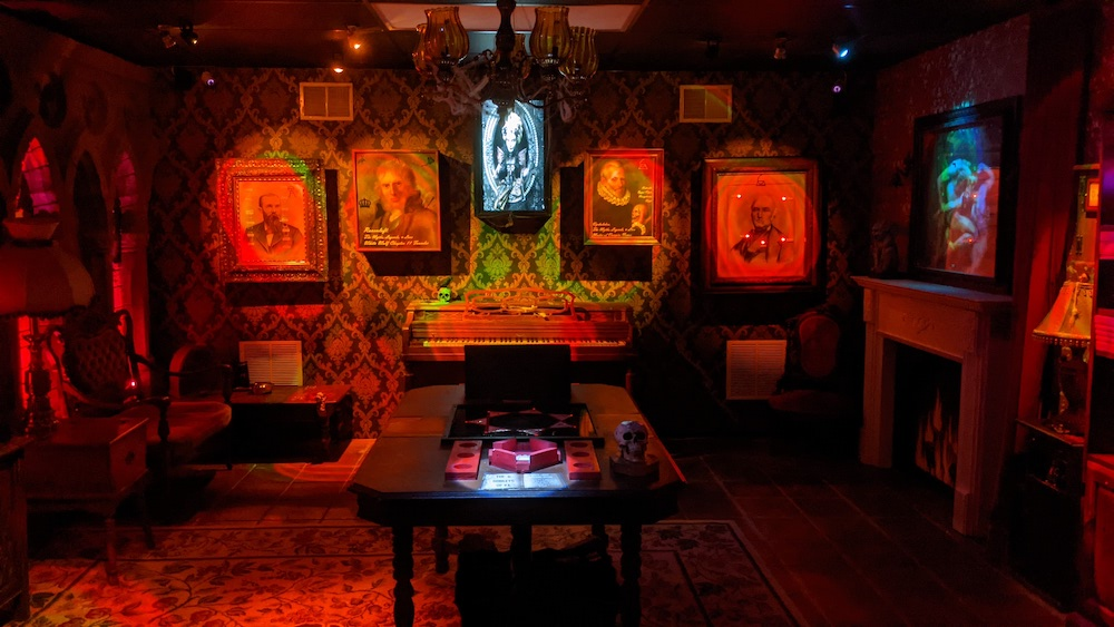 A parlor filled with portraits bathed in red light.