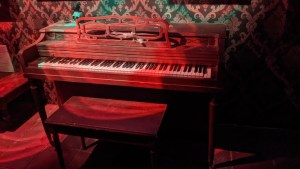 An old piano with a skull and raven sitting atop it.