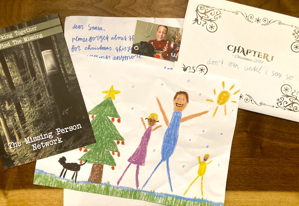 An assortment of items and letters from Dear Santa Chapter 1, including a child's drawing of his family.