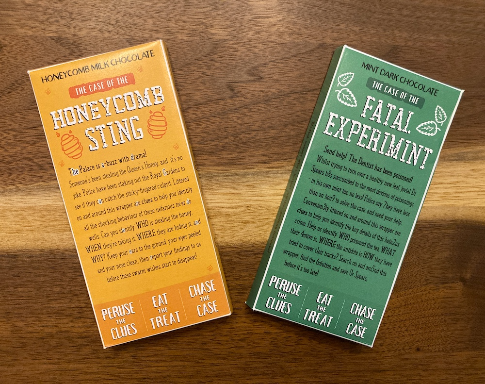 """Packaging for two individual chocolate bars: green, labeled, """"Mind Dark Chocolate, The Case of the Fatal Experiment."""" Yellow labeled, """"Honeycomb Milk Chocolate, The Case of the Honeycomb Sting."""""""