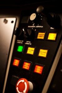 An illuminated control panel with red, yellow, and green buttons.