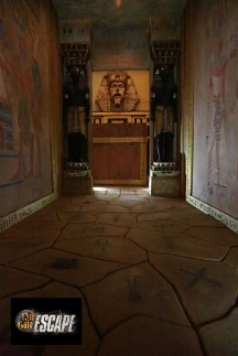 In-game: A hallway in an Egyptian tomb with statues of Anubus, and symbols painted on the stone floor.