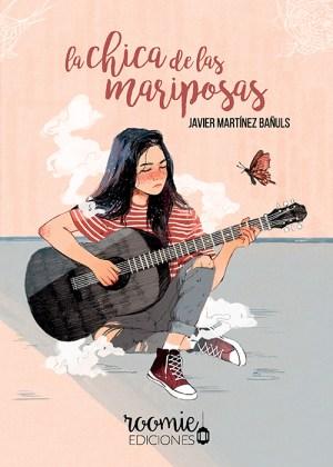 Chica de pelo moreno sentada en el suelo con las piernas cruzadas y tocando una guitarra. Sus vaqueros están rotos y tiene la mirada triste