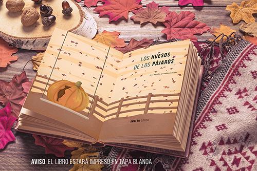 Mockup del libro abierto. Aparece el título (Los huesos de los pájaros) y una calabaza (con un pájaro tallado) colgando en una especie de columpio sobre un cielo con hojas moradas. Todo a color.