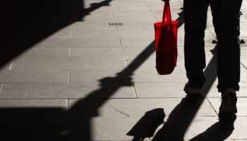 anonymous man walking along sidewalk