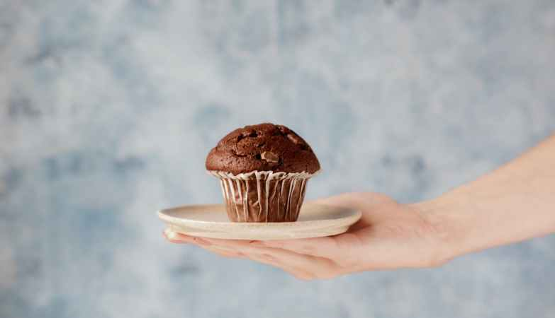 photo of person holding a plate of chcolate muffin