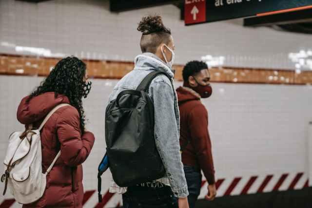 faceless multiethnic students in masks walking in metro
