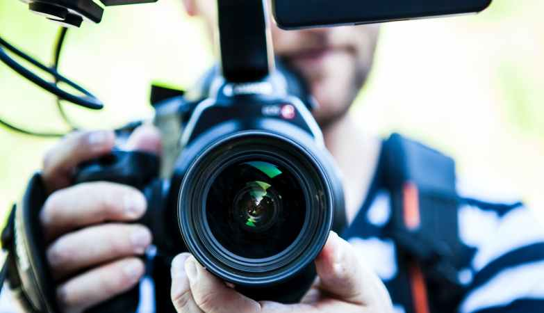 person holding canon dslr camera close up photo