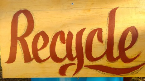 "They needed ""Recycle"" signs so I found a piece of wood then Hand wrote and painted on the spot."