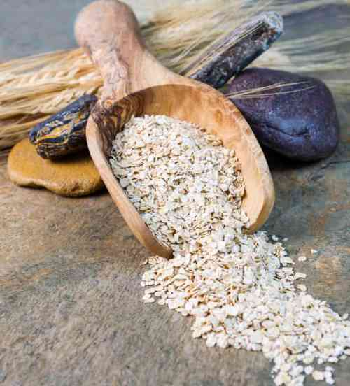 Dry Oat Cereal in wooden spoon on Stone setting