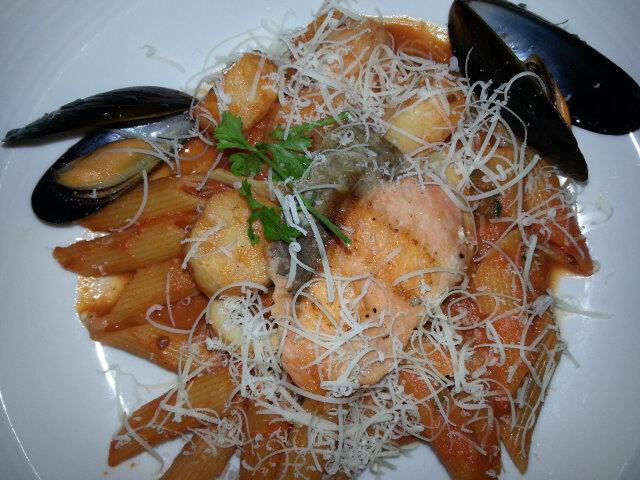 Salmon, scallops, muscles, clams, and shrimp on penne pasta