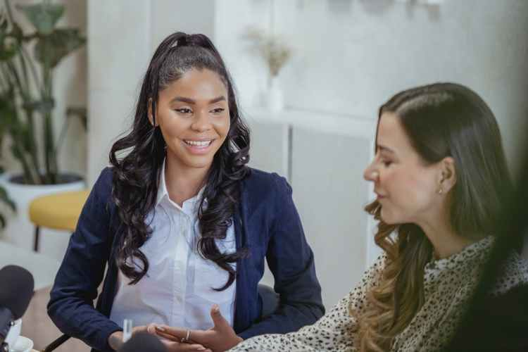 cheerful diverse women having conversation during interview