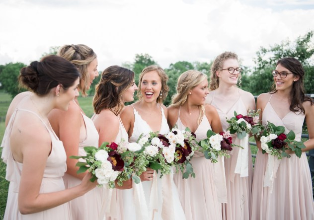 bridesmaids wearing blush bridesmaid dresses holding spring bouquets