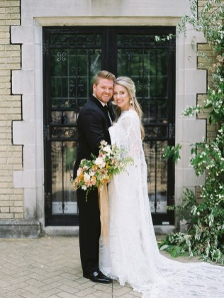 a bride and groom pose in front of their ceremony installation filled with greenery and flowers the bride has on a long and flowy lace wedding dress and is holding her bridal bouquet willed with butterfly ranunculus and spring flowers