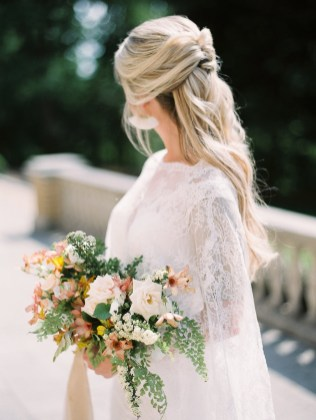 a bride wears her wedding cape over her wedding gown while carrying her bridal bouquet filled with amazing spring flowers