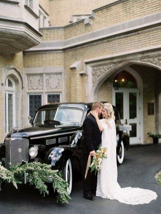 a bride and groom share a tender moment in front of their getaway car before leaving their wedding. The car has a spirea garland on the front bumper. The bride wears a long lace wedding dress and holds her bridal bouquet. The groom wears a black tux.