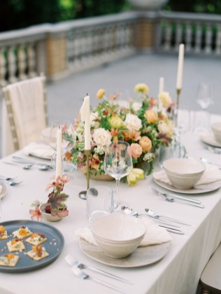 food and flowers grace a banquet reception table on an outdoor balcony on a spring day.