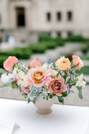 a colorful spring filled centerpiece outside on a table in a courtyard filled with garden roses and ranunculus