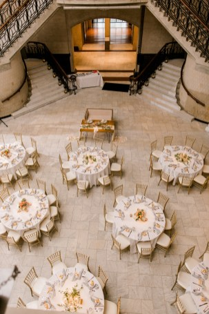 looking down at the great hall are round tables filled with greenery and spring flowers