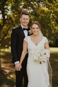 The bride and groom pose on the property of Richwood on the River, a great Kentucky wedding venue. The Bride is holding her bridal bouquet which has white and blush flowers.