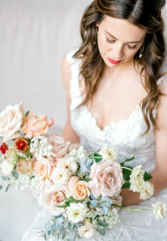 bold red lip bride with pearl earrings and loose curled hair looks at bridal bouquet filled with quicksand roses shimmer roses majolica spray roses blue delphinium white orlaya and red butterfly ranunculus made by cincinnati wedding florist roots floral design at hotel covington