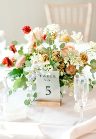 floral centerpiece at hotel covington on while linen with fogged table numbers and beautiful flowers.
