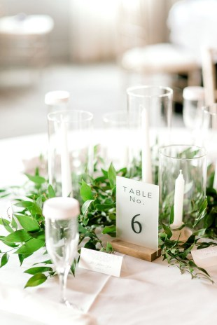 greenery and taper candles on white linen table at hotel covington with table numbers