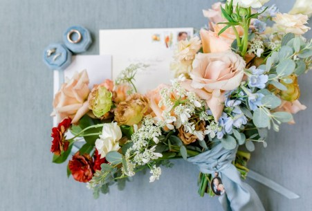 a bridal bouquet laying on top of the wedding invitations in a flat lay with dusty blue ring box