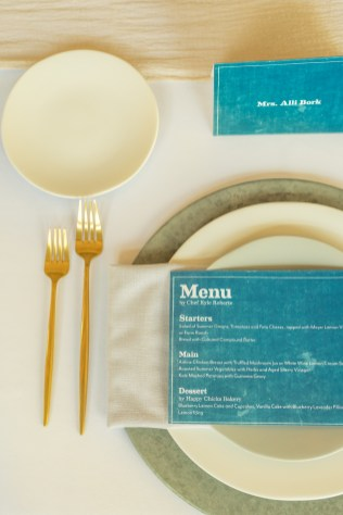 white linen table with blue place cards and menus with concrete chargers and gold flatware at the factory events with cincinnati wedding florist roots floral design