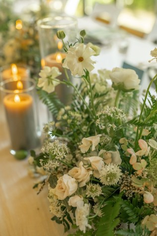 textural white and green floral centerpieces line the white linen table with grey pillar candles in glass hurricanes at the factory events with cincinnati wedding florist roots floral design
