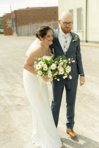 groom with navy suit and floral tie with textural boutonniere holds the bride with her bouquet by cincinnati wedding florist roots floral design