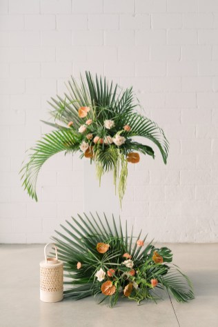 lush tropical arrangement by wedding florist in cincinnati roots floral design sits on a white stand with lower tropical arrangement on botton