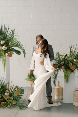 african american couple share a kiss in the middle of their tropical flower installation with wicker lanterns. Bride is wearing off the shoulder wedding gown with buttons down the front. Flowers are by cincinnati wedding florist, Roots floral design
