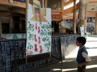 A boy looks inquisitively at a poster about women's violence at our first location - Palampur.